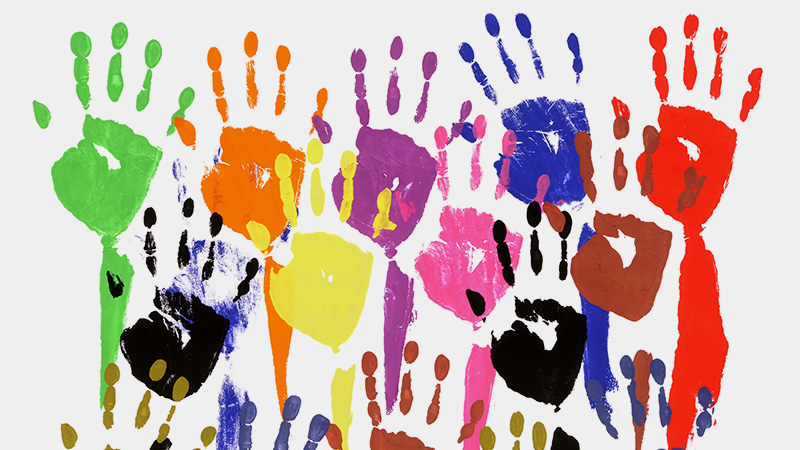 A wall of colourful children's hand-prints (as if the children dipped first in different coloured paints and then pressed them onto the wall)